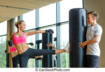 smiling woman with personal trainer boxing in gym - sport,...