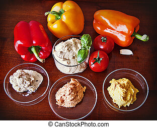 hummus with red, yellow and orange bell peppers ready to dip...
