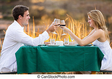 beautiful young couple having romantic dinner by the lake