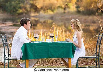 young couple having romantic dinner outdoors