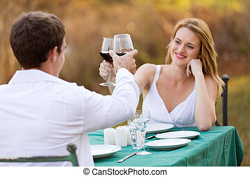 young couple toasting - romantic young couple toasting with...