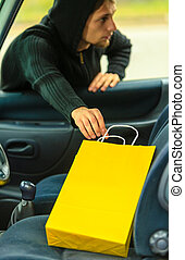 thief stealing shopping bag from the car - Transportation,...
