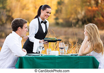 waitress pouring wine for romantic couple - friendly female...