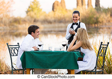 young couple place dinner order to waitress - beautiful...