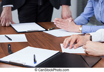Hands and clipboards during business meeting - Close-up of...