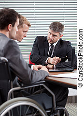 Disabled man and his co-worker talking with boss, vertical