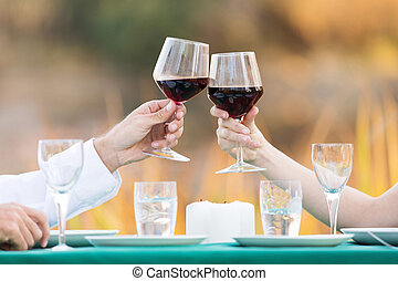 couple toasting with red wine - close up of young couple...