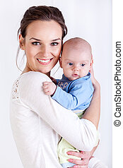 Young mother holding her baby - Woman holding a new born...