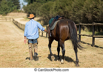 cowboy walking with his horse - rear view of cowboy walking...