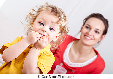 Eating child with mother behind - Young kid eating with...