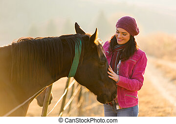 woman touching horse in the paddock - beautiful woman...
