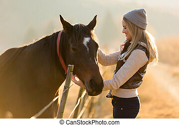 woman petting horse in the farm - pretty woman petting horse...