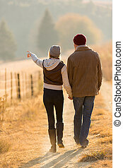 couple walking in country road - rear view of young couple...