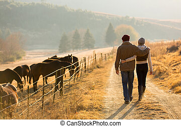 young couple walking in farm road - back view of young...