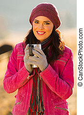 young woman drinking coffee outdoors