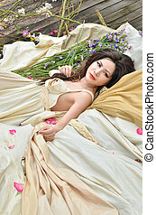 Young beautiful woman lie down with flowers outdoor