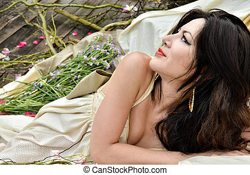 Young beautiful woman lie down with flowers outdoor and...