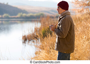 thoughtful man standing by lake and drinking coffee in...