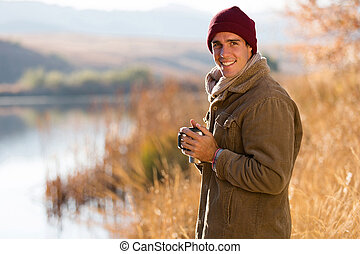 man drinking coffee outdoors in fall - portrait of happy man...
