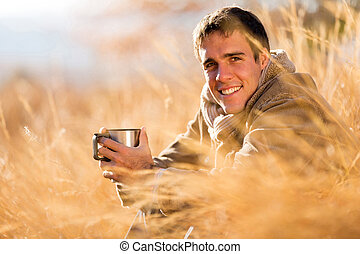 young man drinking coffee in fall - cheerful young man...