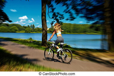 Back of sexy hot sport blond woman girl model  riding on bicycle in the green summer park near lake with flying elevated hair in air