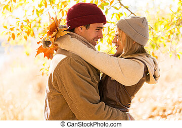 couple hugging in autumn park - cheerful couple hugging in...