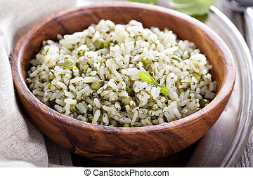 Green rice with herbs in wooden bowl
