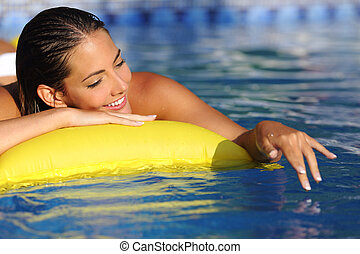 Woman bathing and playing with water on a swimming pool in...