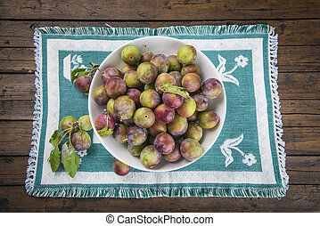Fruit bowl with greengage plums on a green tablecloth