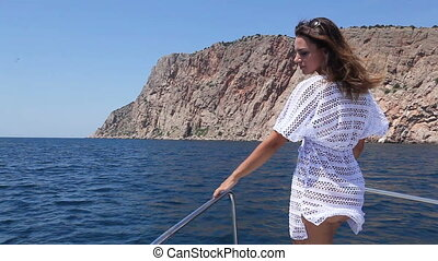 Girl in dress on nose of yacht - Standing on yacht of nose...