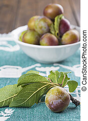 Closeup from ecological plums with a fruit bowl behind