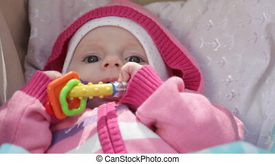 Baby lays in a carriage and plays with a rattle