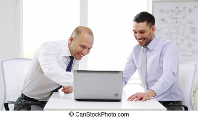 two smiling businessmen with laptop in office - business,...