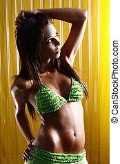 stunning woman wearing green bikini on yellow background