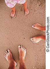 family footprints in the sand on the beach