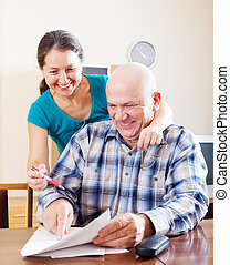 Joyful mature couple reading financial documents at home...