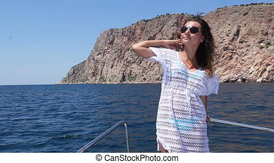 Girl in dress on nose of yacht