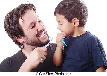 Father teaching his son how to clean the teeth - Father is...