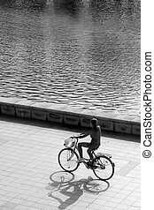 backlit silhouette of girl riding a bike , black and white