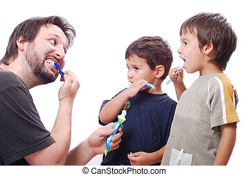 Young man teaching kids how to clean the teeth - Father is...