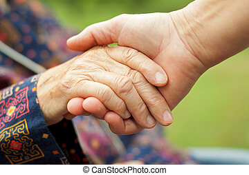 Help giving - Doctor's hand holding a wrinkled elderly hand