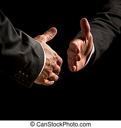Business handshake - Hands of two businessmen reaching out...
