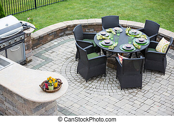 Elegant outdoor living space on a paved brick patio with a...