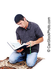 Muslim man is holding holy book Qoran and praying on traditional way