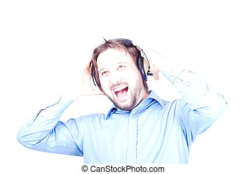 Young man with headphones on head smiling and shouting -...