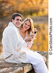 couple wrapped in blanket and enjoying wine at sunset -...