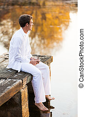 young man sitting on wooden pier by the lake