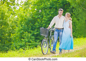 Young Caucasian Couple Having a stroll in Park with Bike