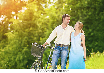 Portrait of  Caucasian Couple Having a Stroll in Park with Bike.