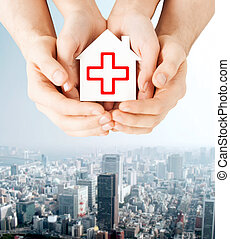 hands holding paper house with red cross - healthcare,...